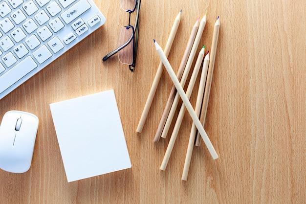 Bedrijfsvoorwerpen van toetsenbord, muis, potloden, witboeknota, en glazen op houten bureau voor bedrijfsachtergrond en ontwerp