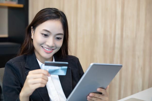 Bedrijfsvrouw aziatische gebruikende tablet en creditcard die online winkelen
