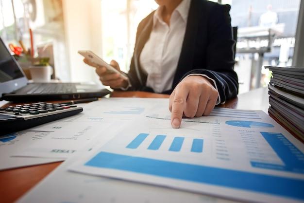 Bedrijfsvrouw bij het werken met financiële rapporten en het gebruiken van mobiele smartphone in het bureau