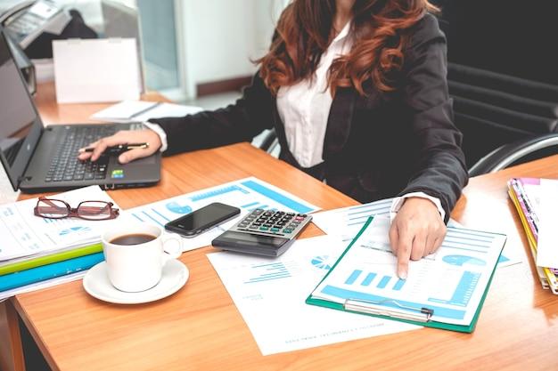 Bedrijfsvrouw bij het werken met financiële rapporten en laptop computer in het bureau.