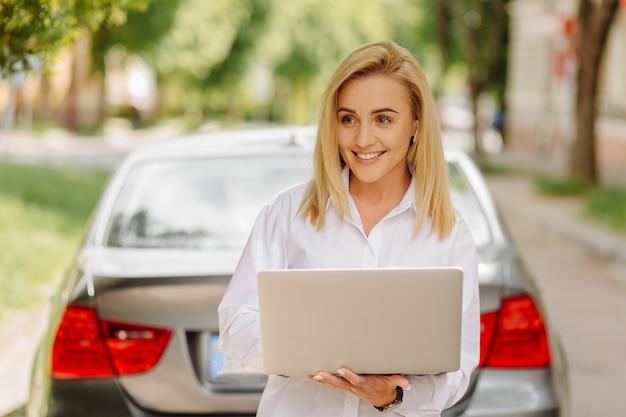 Bedrijfsvrouw die aan laptop computer buiten in stadspark werken