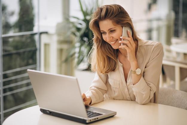Bedrijfsvrouw die aan laptop werkt en op de telefoon spreekt