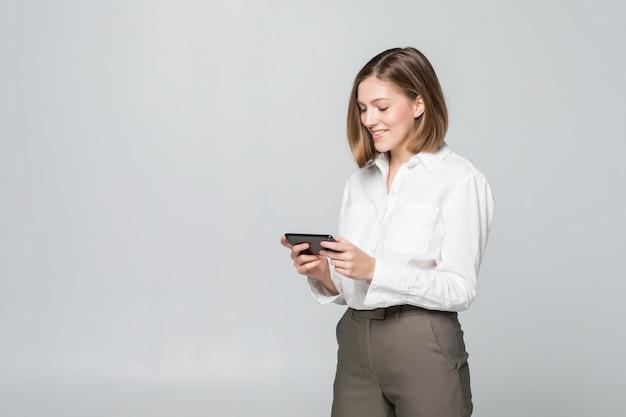 Bedrijfsvrouw die app op een slimme telefoon over witte muur gebruiken