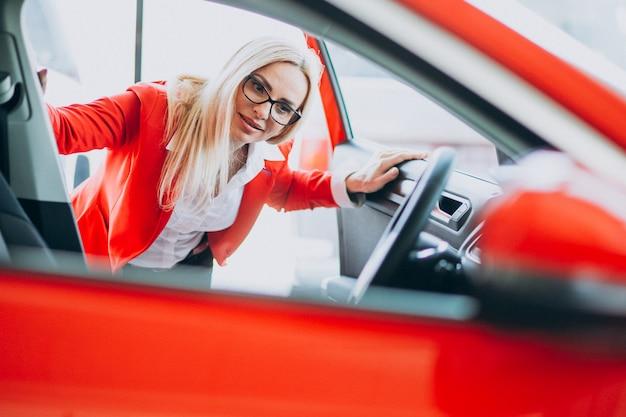 Bedrijfsvrouw die auto zoeken mobiel bij een autoshowroom
