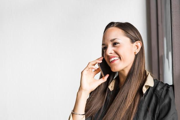 Bedrijfsvrouw die bij de telefoon met exemplaarruimte spreken