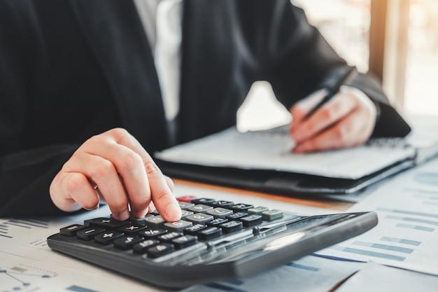 Bedrijfsvrouw die boekhouding met calculator doen