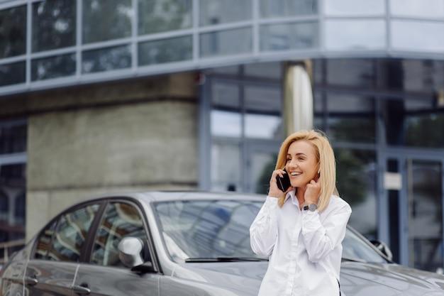 Bedrijfsvrouw die de slimme telefoon buiten bureaucentrum met behulp van