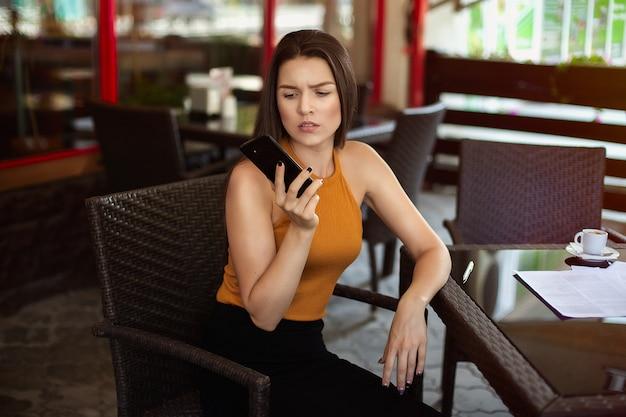 Bedrijfsvrouw die de telefoon in een koffie bij een lijst met verspreide documenten op de lijst en een kop van koffie bekijken. slecht nieuws, bezorgdheid.