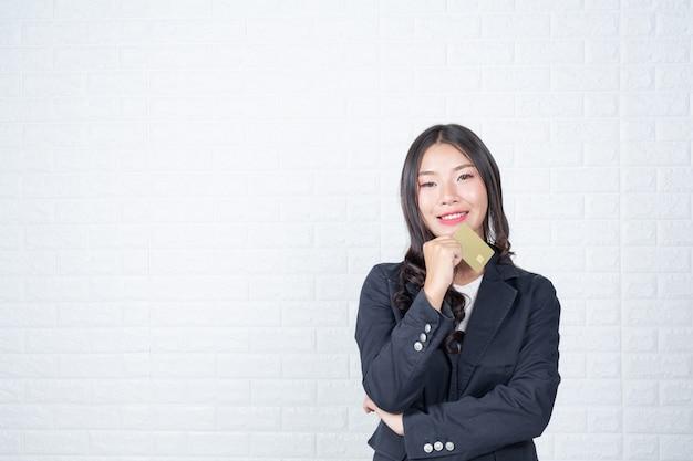 Bedrijfsvrouw die een afzonderlijke contant geldkaart, witte bakstenen muur houden maakte gebaren met gebarentaal.
