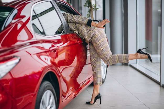 Bedrijfsvrouw die een auto byet