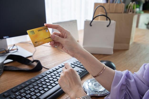 Bedrijfsvrouw die een creditcard voor betaling houden thuis winkelend.
