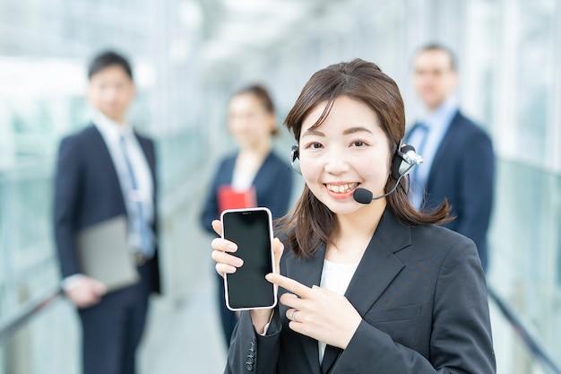 Bedrijfsvrouw die een hoofdtelefoon draagt en op een smartphone richt