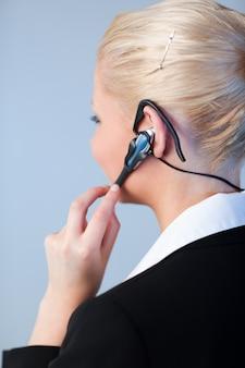 Bedrijfsvrouw die een hoofdtelefoon met behulp van