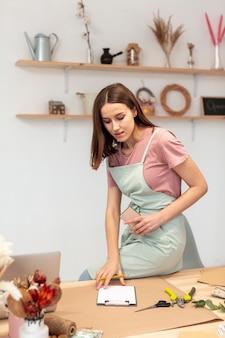Bedrijfsvrouw die een klembord in haar eigen winkel gebruiken