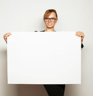 Bedrijfsvrouw die een leeg aanplakbord houden.