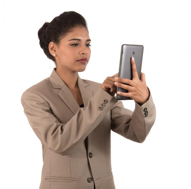 Bedrijfsvrouw die een mobiele telefoon of een smartphone gebruiken die op een witte ruimte wordt geïsoleerd