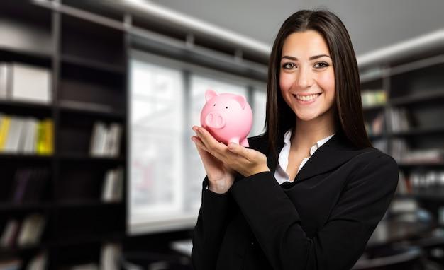 Bedrijfsvrouw die een spaarvarken houden