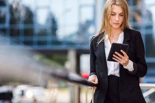 Bedrijfsvrouw die een tablet in openlucht gebruiken