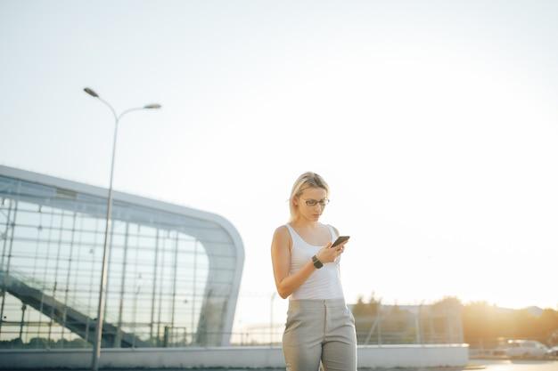 Bedrijfsvrouw die een telefoon en een klok gebruiken terwijl status in openlucht