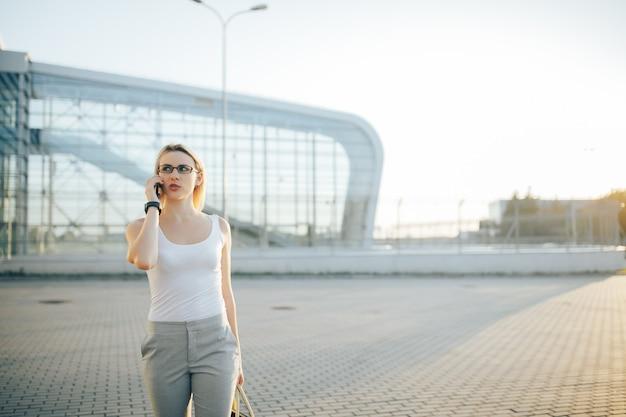 Bedrijfsvrouw die een telefoon met behulp van terwijl status in openlucht