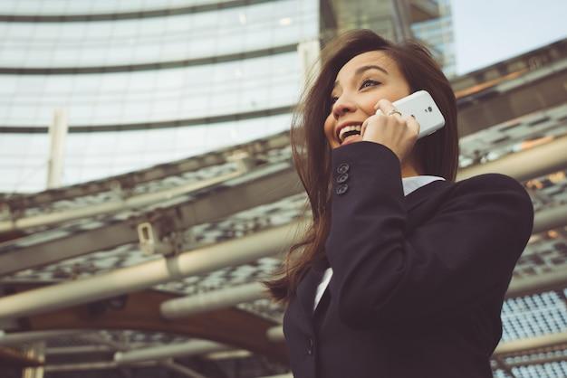Bedrijfsvrouw die een telefoongesprek buiten het bureau maken