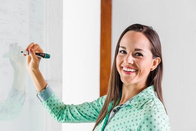 Bedrijfsvrouw die en op whiteboard glimlachen schrijven