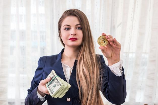 Bedrijfsvrouw die gouden bitcoin en dollarbos tonen