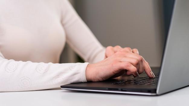 Bedrijfsvrouw die haar laptop voor haar bloemenwinkel met behulp van