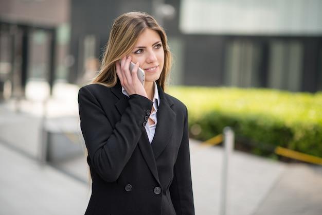 Bedrijfsvrouw die haar mobiele telefoon met behulp van