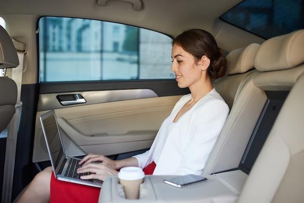 Bedrijfsvrouw die in auto werken
