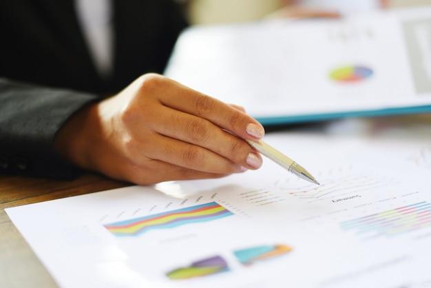 Bedrijfsvrouw die in bureau met het controleren van bedrijfsrapport aan de lijst van het lijstbureau / het voorbereiden van rapportgeld werken die grafieken analyseren