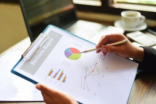 Bedrijfsvrouw die in bureau met het controleren van bedrijfsrapport aan de lijstbureau werken met calculatorsmartphone en koffiekop - het voorbereiden van rapportgeld die grafiekengrafiek analyseren