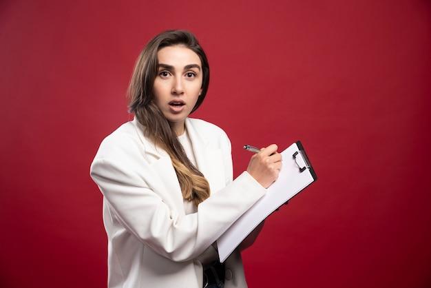Bedrijfsvrouw die in een notitieboekje schrijft