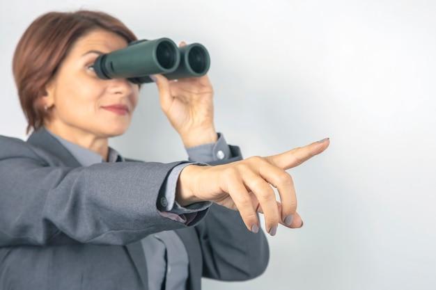 Bedrijfsvrouw die in kostuum door verrekijkers kijken