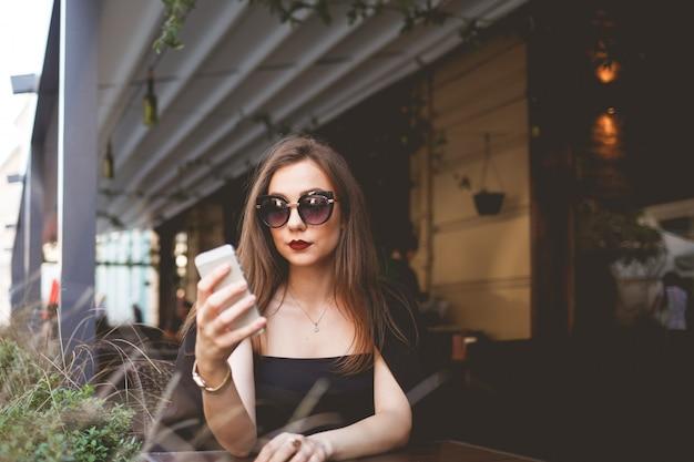 Bedrijfsvrouw die in zonnebril met een telefoon in haar handen bij een restaurantlijst zitten