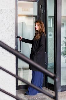 Bedrijfsvrouw die in zwart jasje de bouw ingaat