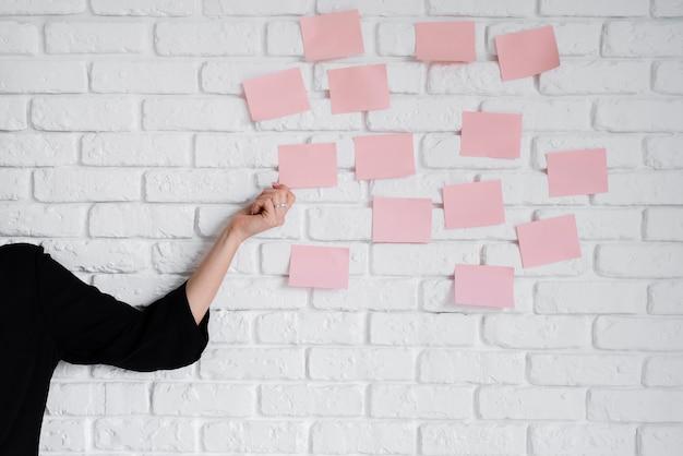 Bedrijfsvrouw die kleverige nota's over muur plakken