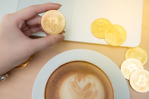 Bedrijfsvrouw die koffie / thee drinken en laptop in bureau, in hand bitcoin met behulp van