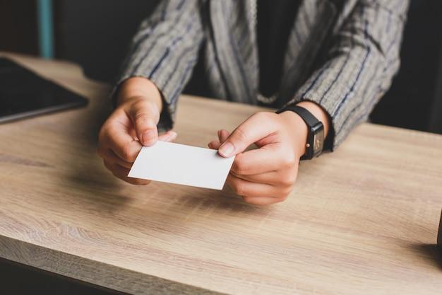 Bedrijfsvrouw die lege witte zaken of naamkaart geven aan bureaulijst