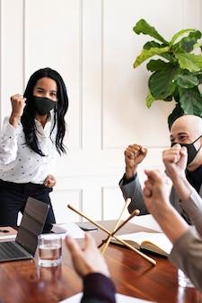 Bedrijfsvrouw die masker draagt in coronavirusvergadering