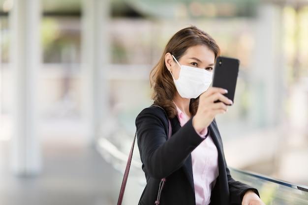 Bedrijfsvrouw die masker verkleden met telefoon dragen.