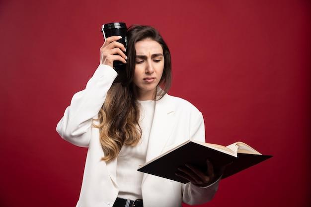 Bedrijfsvrouw die met een kop op een notitieboekje kijken