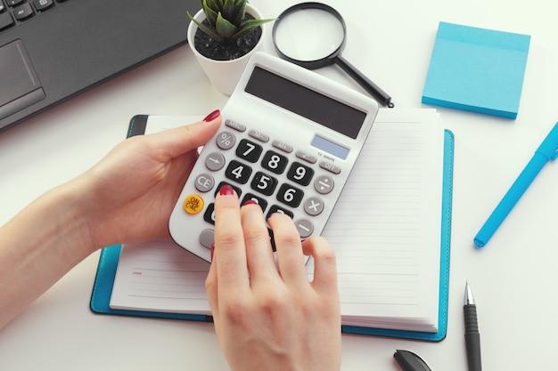 Bedrijfsvrouw die met financiële gegevenshand werken die calculator gebruiken