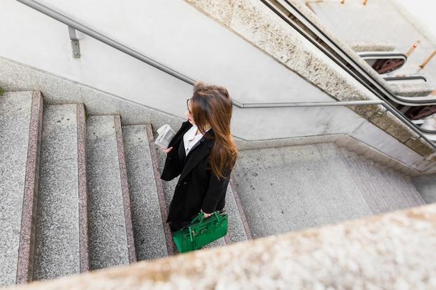 Bedrijfsvrouw die met krant en zak trappen loopt