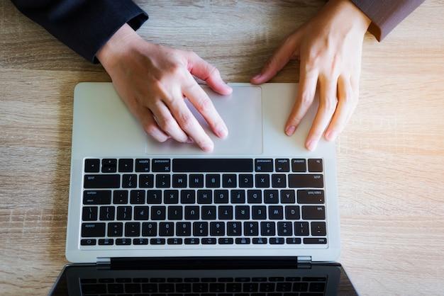 Bedrijfsvrouw die met laptop aan lijstbureau werken.