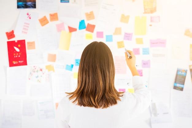 Bedrijfsvrouw die met nota's in een bureau werken