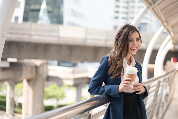 Bedrijfsvrouw die mooi glimlachen die een kop van koffie houden