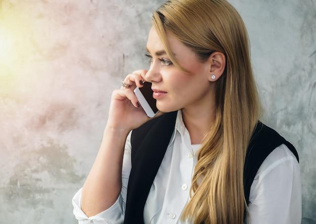 Bedrijfsvrouw die op de telefoon met een smartphone spreken.