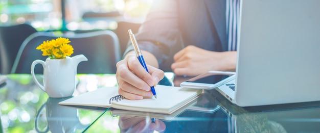 Bedrijfsvrouw die op een notebookwith een pen in het bureau schrijven