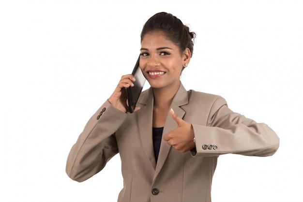Bedrijfsvrouw die op mobiele telefoon spreken en duim tonen geïsoleerd op witte ruimte.